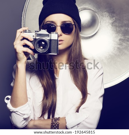 Hipster girl in points and a cap with a camera - stock photo