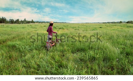 Hipster girl in straw hat walking with bicycle on summer meadow outdoor - stock photo