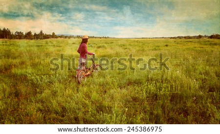 Hipster girl in straw hat walking with bicycle on summer meadow outdoor. Vintage image - stock photo