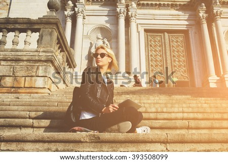 Hipster girl in sunglasses is looking away, while is sitting with touch pad against old architectural building. Young woman tourist is holding digital tablet, while is resting after tour in museum  - stock photo