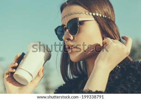 Hipster girl in sunglasses with cup of coffee. Close-up lifestyle outdoor portrait - stock photo
