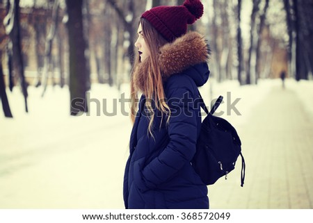 Hipster girl in warm down jacket , knit hat with a pompom color marsala and travel backpack. Photo toned style Instagram filters. - stock photo