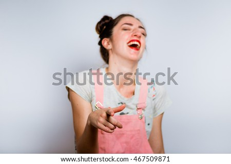 hipster girl mocking someone dressed in a pink suit, isolated on white background