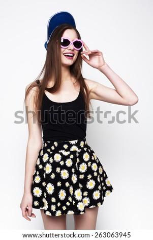 Hipster girl portrait. Studio shot of pretty model on grey background - stock photo