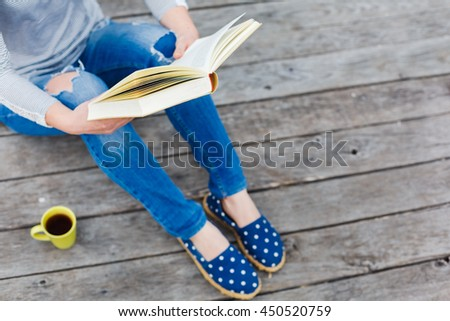 hipster girl reading open book on a wooden floor