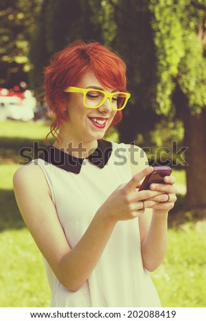 Hipster girl text messaging on her smart phone , toned image - stock photo