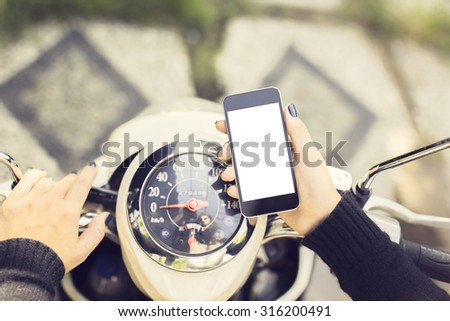 Hipster girl with a blank phone and a motorbike - stock photo