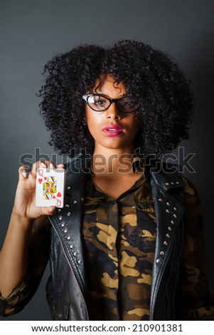 Hipster girl with afro wearing camouflage and leather holding queen of hearts card