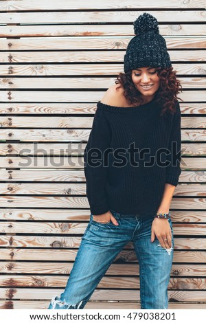 swagger style for girls. hipster girl with curly hair wearing black sweater, hat and jeans posing against wooden wall swagger style for girls g