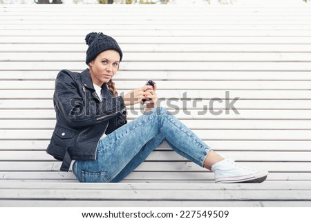 Hipster girl with phone sitting on a white bench in the park.  Outdoors lifestyle portrait of  woman looking at camera - stock photo