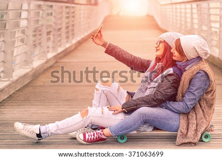 Hipster girlfriends taking a selfie in urban city contest seat on skate - Concept of friendship and fun with new trend and technology - Best friends eternalizing the moment with modern smartphone - stock photo