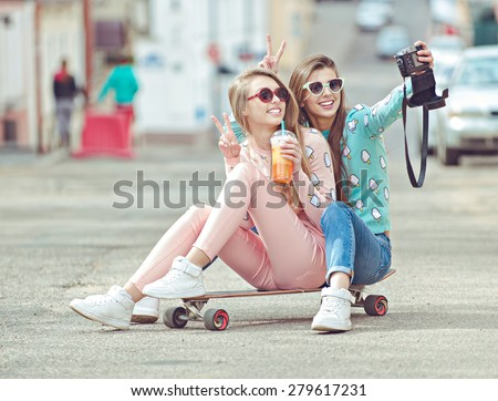 Hipster girlfriends taking a selfie in urban city context, Concept of friendship and fun with new trends and technology.  Best friends eternalizing the moment with modern digital camera - stock photo