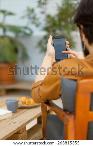hipster guy using his smart phone outdoors and relaxing.shallow depth of field with focus on the hand - stock photo