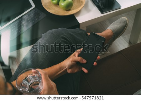 hipster hand using smart phone for mobile payments online business,glass of water,sitting on sofa in living room,green apples in wooden tray,filter