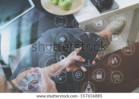 hipster hand using smart phone for mobile payments online business,glass of water,sitting on sofa in living room,green apples in wooden tray,graphic interface icons virtual screen