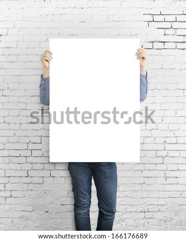 hipster holding poster on concrete brick wall - stock photo