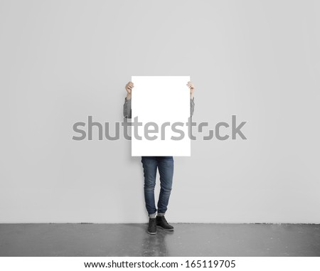 hipster holding poster on concrete floor - stock photo
