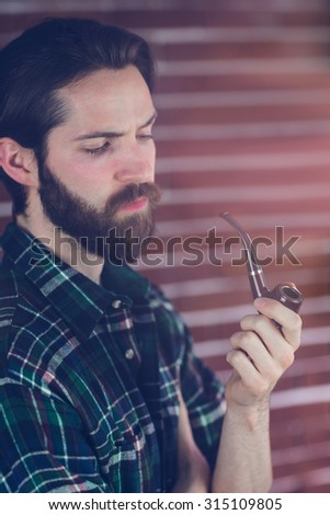 Hipster holding smoking pipe against brick wall