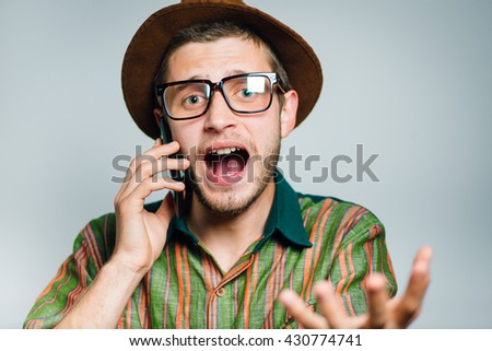 hipster man annoyed on the phone, wearing a hat and glasses, isolated on a gray background