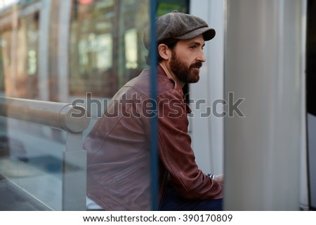 Hipster man dressed in a brown leather jacket and stylish hat is sitting on a bench outdoors in spring day, bearded adult male is thinking about something while waiting for a someone in the fresh air - stock photo