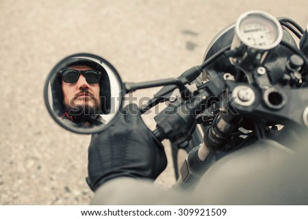 Hipster man driving vintage style custom motorcycle on the road.The reflection in the mirror of a man with a beard wearing a helmet and sunglasses
