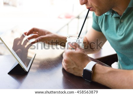 Hipster man hands working on digital tablet and  drinking cold coffee cocktail, business person browsing internet or connecting to wireless via touchscreen pad. He is sitting in a cafe .