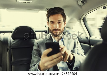 Hipster man in car. Typing text message on mobile phone. Filter vintage - stock photo