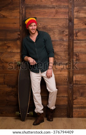 Hipster man in hat standing over wooden background. Happy skateboarder stansing near skateboard.