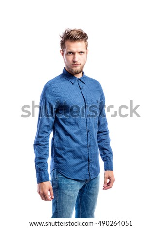 Hipster man in jeans and blue shirt, studio shot, isolated