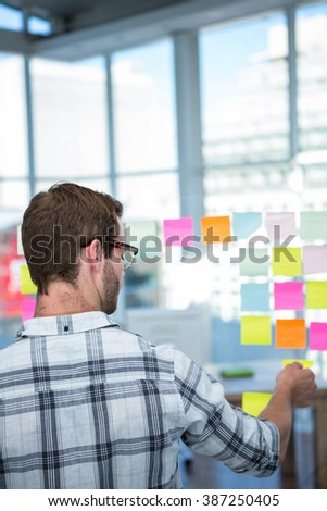 Hipster man looking at post-it in office - stock photo