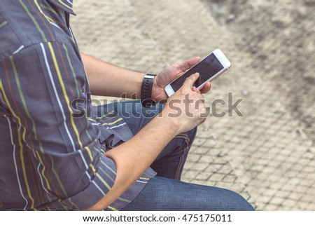 Hipster man playing smart phone, mobile, telephone.