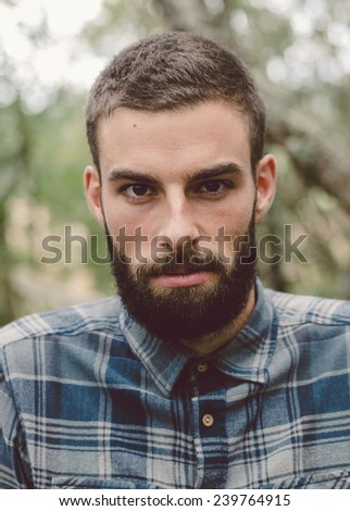 Hipster man portrait. Man has beard and he is outdoor. - stock photo
