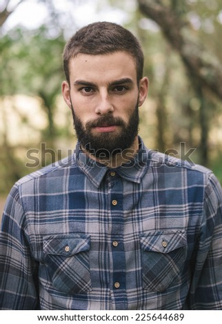 Hipster man portrait outdoors. Man is looking at camera. - stock photo