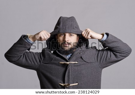 Hipster man posing in studio shot with hood on head and winter clothes
