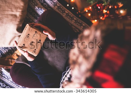 Hipster man putting Christmas present, under Christmas tree. Depth of field, selective focus - stock photo
