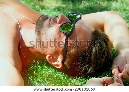 Hipster man relaxed and lying on the grass in city park,in sun reflecting sunglasses,mans fashion style.Sportsman with sexy fit body rest. Summer concept.Carefree young beard man lying on grass - stock photo