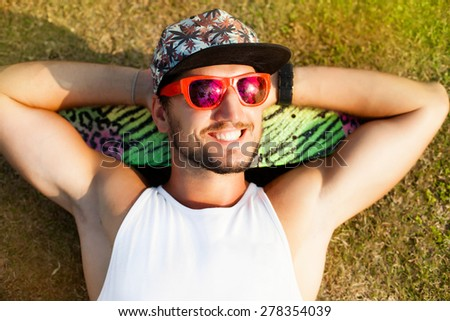 hipster man relaxed and lying on the grass on a tropical island,in sun reflecting bright sunglasses and skateboard.smiles and laughs,mans fashion style.Stylish young beard man,hipster outfit. - stock photo