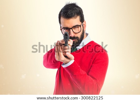 Hipster man shooting with a pistol over ocher background