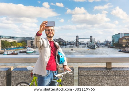 Hipster man taking a selfie in London with Tower Bridge on background. He is commuting, he has a fixed gear bike and holds the helmet with the arm. Lifestyle, travel and sustainability concepts. - stock photo
