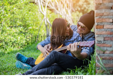 how to hold a guitar while sitting