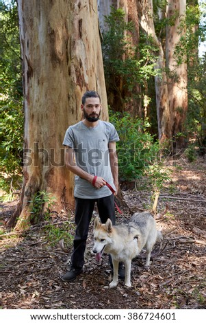 Hipster man with beard poses for a portrait with his pet husky dog while taking a walk in a forest