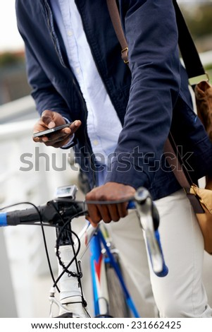 Hipster man with bicycle sending message on mobile cell phone in urban city - stock photo