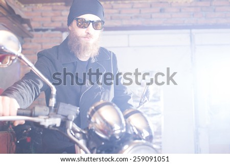 Hipster man with his chopper motorcycle posing. - stock photo