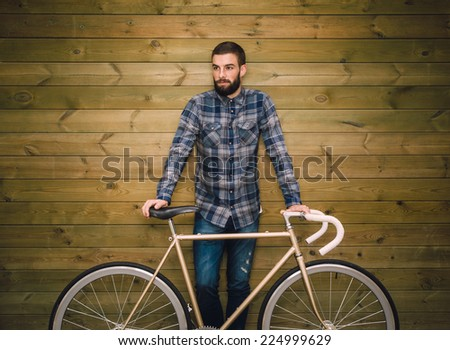 Hipster man with his fixie bike on a wooden background