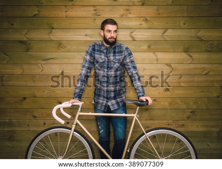 Hipster man with his fixie bike on a wooden background - stock photo