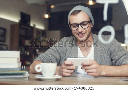 Hipster man with mobile phone at cafe   - stock photo