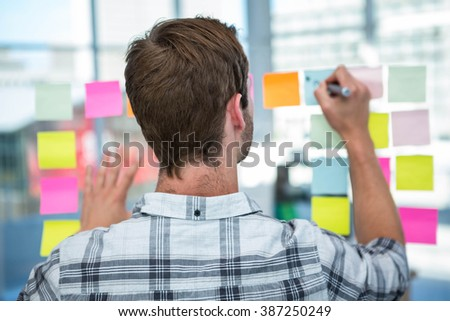 Hipster man writing on post-it in office - stock photo