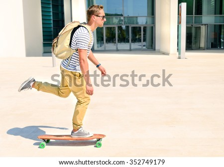 Hipster men going to  study in city with an alternative and ecologic way. Concept of carefree youth and freedom outdoors against city background. Active guy enjoying everyday life moments doing sport - stock photo