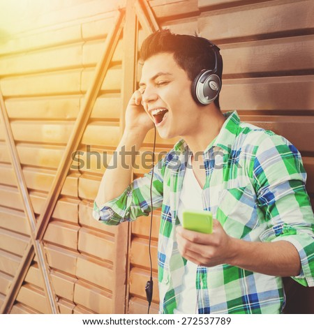 Hipster mixed race young man singing. Closeup of handsome guy with headphones and smartphone in green plaid shirt listening to music. Natural light, retouched, filter applied, square format. - stock photo
