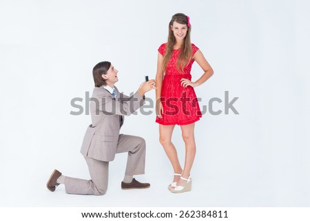 Hipster on bended knee doing a marriage proposal to his girlfriend on white background - stock photo